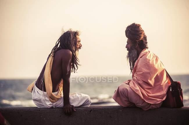 Two male yogis talking at coast in Kanyakumari, South India, India, Asia — Stock Photo