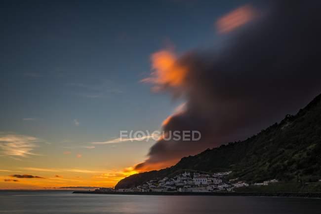 Pequeño pueblo por el mar en el atardecer con nubes dramáticas en Ribeira Quente, Portugal - foto de stock
