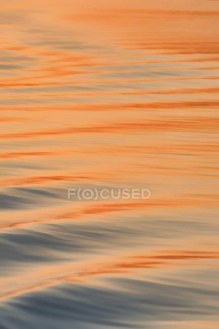 Wave pattern on river surface at sunset, full frame — стоковое фото