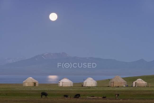 Levantamiento de la luna sobre yurtas nómadas en la orilla del lago en Naryn, Kirguistán, la provincia Asia - foto de stock