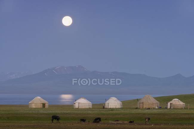 Moon rising over nomad yurts on lake shore in Naryn province, Kyrgyzstan, Asia — Stock Photo