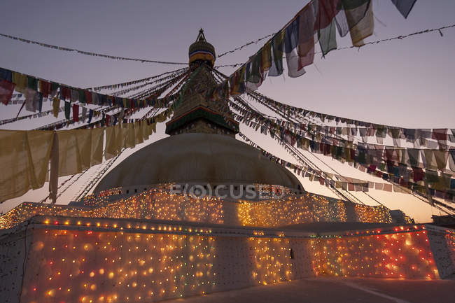 Boudhanath Stupa decorated with prayer flags and lights in evening light, Kathmandu, Nepal, Asia — Stock Photo