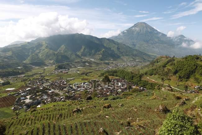 Tieng pueblo con la montaña Trerep y volcán Sindoro en meseta de Dieng, Java, Indonesia, Asia - foto de stock