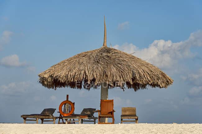 Парасольки, шезлонги та рятувальний круг на пляжі з бунгало на Paradise Island, Мальдіви — стокове фото
