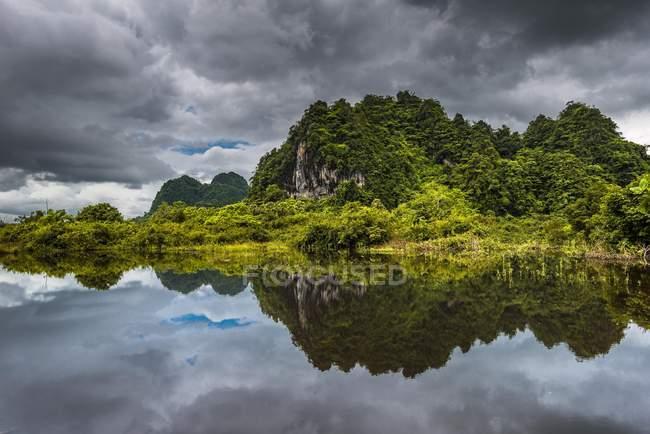 Colline di morfologia carsica con le nubi scure che riflette in acqua in Hpa-an, Myanmar, Asia — Foto stock