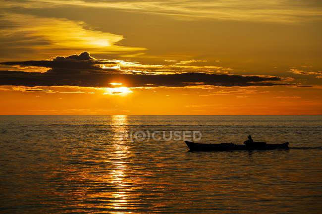 Coucher du soleil et la silhouette de personne en bateau, Sulawesi, Indonésie, Asie — Photo de stock