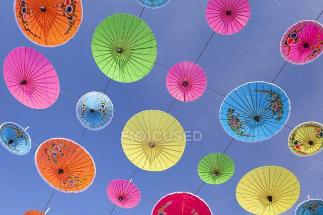 Colorful Asian umbrellas suspended in air against blue sky — Stock Photo