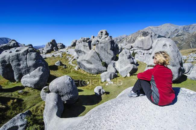 Hiker sitting on limestone outcrops on Castle Hill, South Island, New Zealand, Oceania — Stock Photo