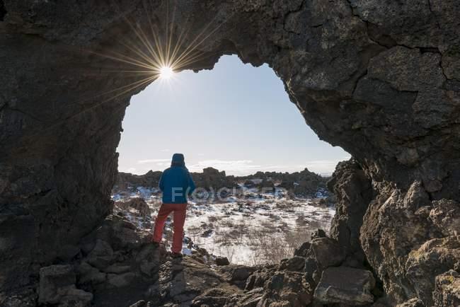 Hombre de pie en el arco de piedra con rayos de sol y paisaje volcánico de Krafla, Parque Nacional de Dimmuborgir, Myvatn, Islandia, Europa - foto de stock