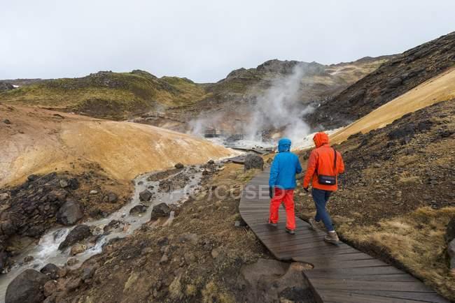 Hombres excursionistas caminando sobre vapor senderismo trail en Seltun área geotérmica, Reserva Nacional de Reykjanesfolkvangur, Islandia, Europa - foto de stock