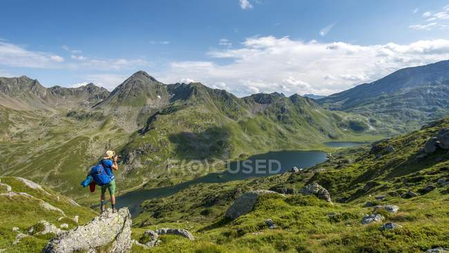 Hiker taking photo in valley on Giglachsee lakes, Schladminger Tauern, Schladming, Styria, Austria, Europe — Stockfoto
