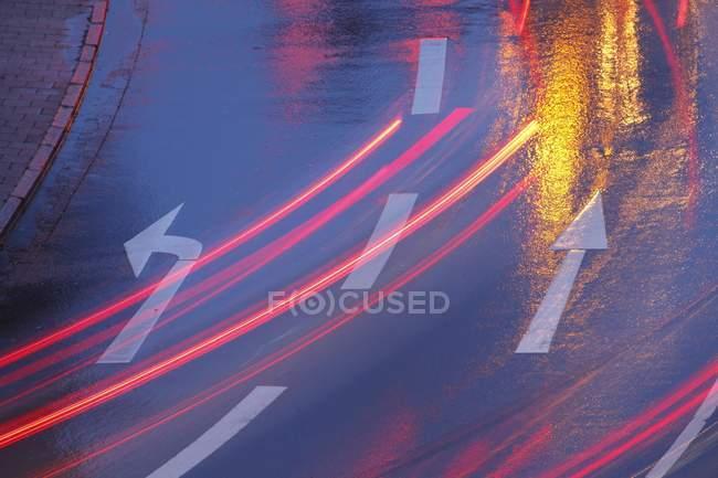 Calle lluvia-mojado con senderos de luces y flechas de dirección en el marco de atardecer, completo - foto de stock