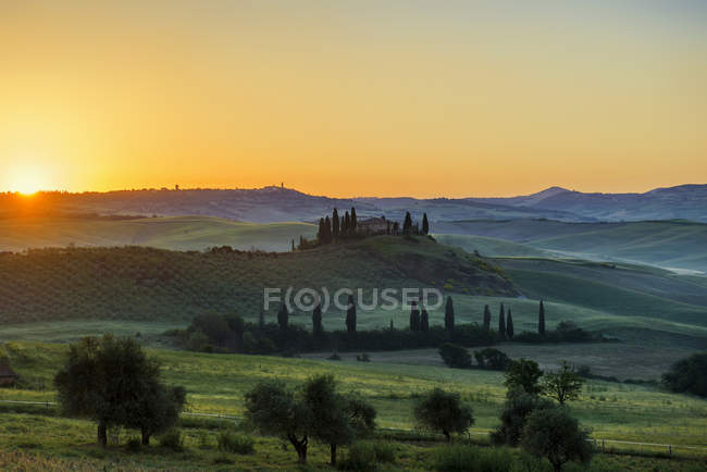 Sunrise over landscape with farmhouse and cypress trees, Val dOrcia, Tuscany, Italy, Europe — Stock Photo