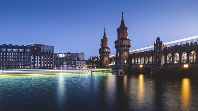 Oberbaum Bridge with light traces from ship and train in twilight, Berlin, Germany, Europe — Stock Photo