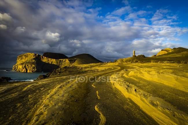 Скалистый берег с дороги и маяк Farol da Ponta dos Capelinhos, Остров Файал, Азорские острова, Португалия, Европа — стоковое фото