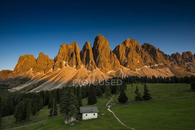 Puesta de sol sobre la choza debajo de las montañas de Villnosstal, Rigais Sass, Dolomitas, Tirol del sur, Italia, Europa - foto de stock