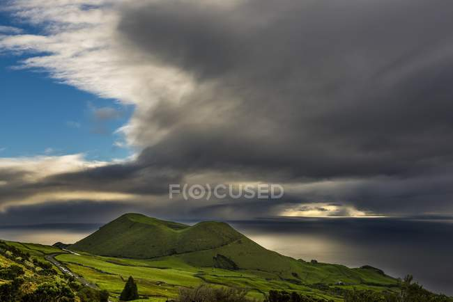 Volcano crater with green meadow and Atlantic coast under cloudy sky, island of Pico, Azores, Portugal, Europe — стоковое фото