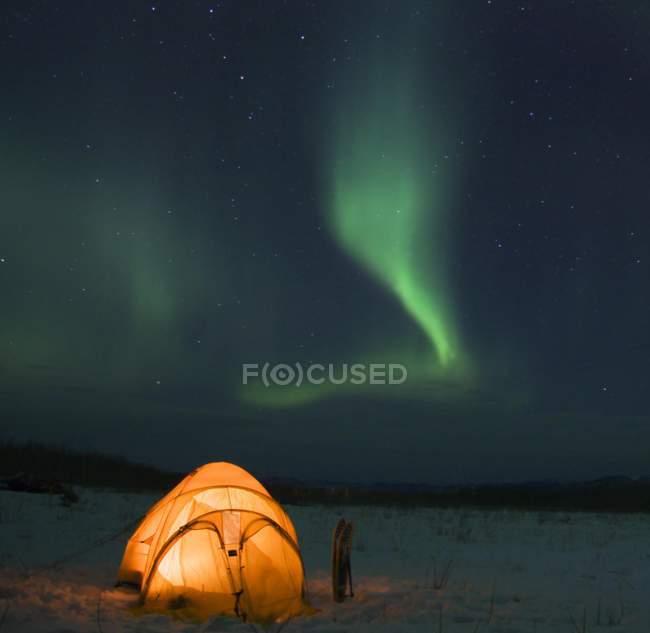 Aurora Boreal sobre el campamento de invierno iluminada tienda, territorio de Yukon, Canadá, América del norte - foto de stock