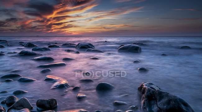 Rocks on beach at sunset by sea, Rugen island, Mecklenburg-Western Pomerania, Germany, Europe — Stock Photo