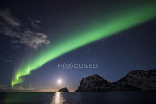 Northern lights over moonlight beach of Haukland, Lofoten, Norway, Europe — стоковое фото