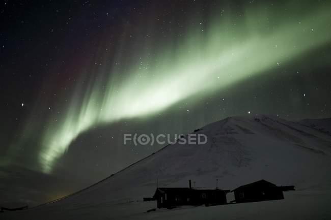 Aurora Boreal verde encima de chozas, Todalen Adventdalen, Spitsbergen, Svalbard, Noruega, Europa - foto de stock