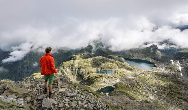 Hiker overlooking clouds over ridge at Schladminger Tauern, Styria, Austria, Europe — Stockfoto
