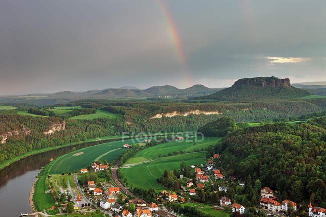 Rainbow over village and forest in Saxon Switzerland National Park, Saxony, Germany, Europe — Stock Photo