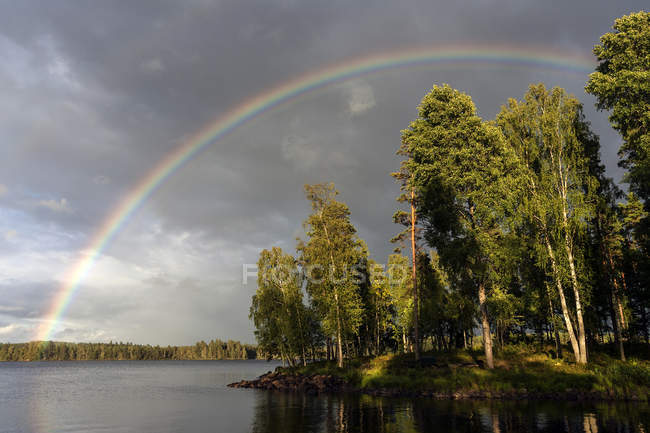 Rainbow over Lake Rusken in storm clouds and evening light, Smland, Sweden, Europe — Stock Photo