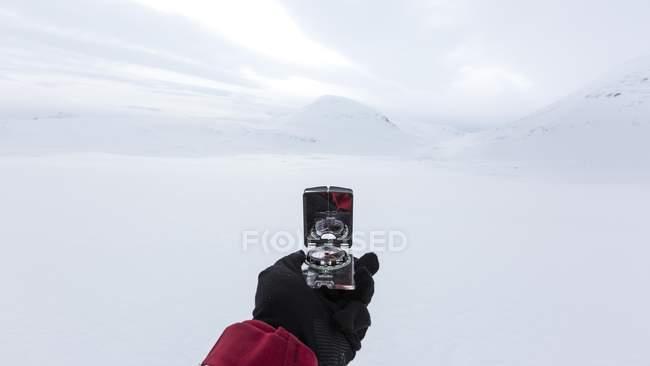 La mano della persona che tiene la bussola di navigazione in inverno, Kungsleden, provincia della Lapponia, Svezia, Scandinavia, Europa — Foto stock