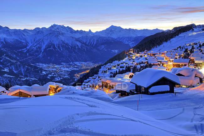 Snow-covered village overlooking Rhone valley towards Dom, Matterhorn and Weisshorn mountains in twilight, Bettmeralp, Aletsch area, Upper Valais, Valais, Switzerland, Europe — Stockfoto
