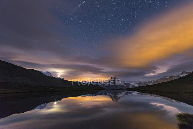 Night view with starry sky and shooting star over snow-covered Matterhorn reflecting in lake, Valais, Switzerland, Europe — стоковое фото
