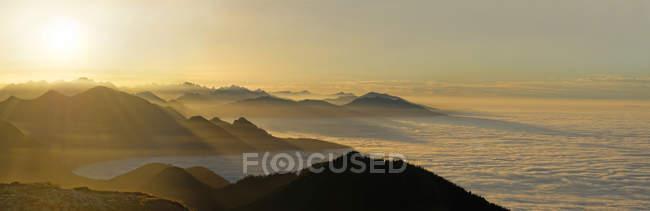 Sonnenuntergang über den Gipfeln der Voralpen im Nebel, Benediktenwand, Bayern, Deutschland — Stockfoto
