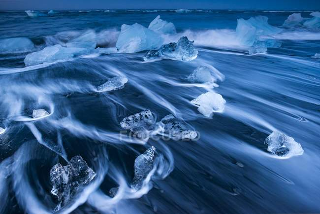 Ice crystals on black beach lapped by sea water, Jokulsarlon Glacier Lagoon, Iceland, Europe — Stockfoto