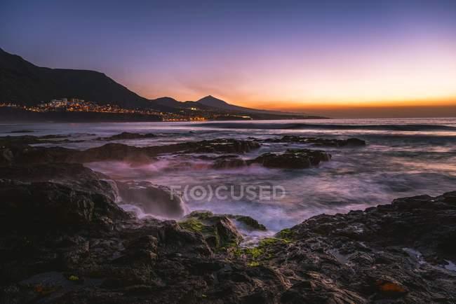 Costa rochosa e mar ao pôr do sol com o vulcão Pico del Teide, Punta del Hidalgo, Tenerife, Ilhas Canárias, Espanha, Europa — Fotografia de Stock