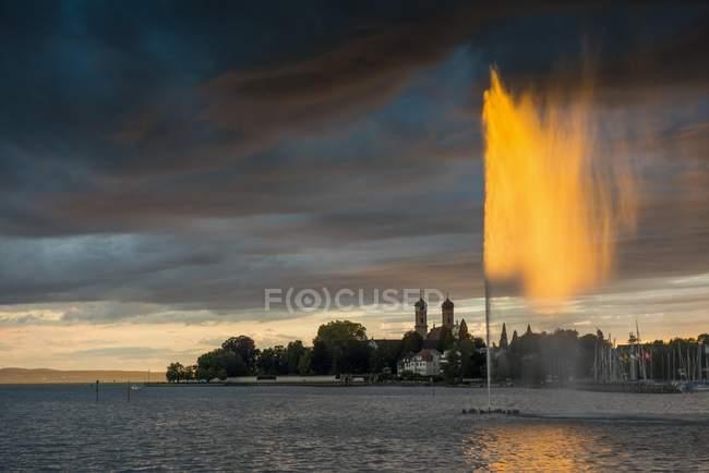 Fuente y nubes de tormenta al atardecer en el lago de Constanza, la Schlosskirche, Friedrichshafen, Baden-Wurttemberg, Alemania, Europa - foto de stock
