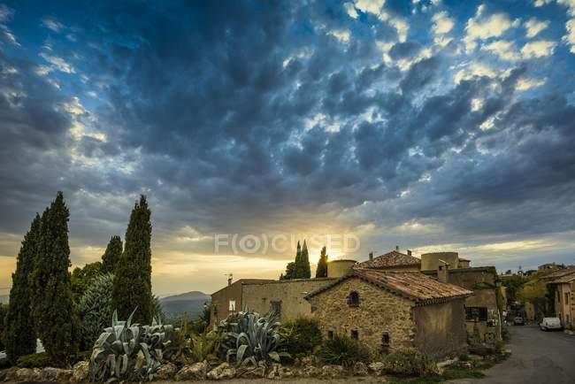 Edificios de la ciudad al atardecer con cielo nublado, Tourtour, Francia, Europa - foto de stock