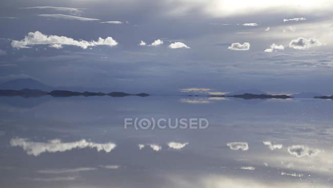 Reflektierenden Wolken bei Sonnenuntergang in Salz See des Salar de Uyuni, Bolivien, Südamerika — Stockfoto