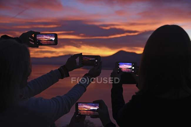 People taking photos of sunset with smartphones near Luino, Lago Maggiore, Lombardy, Italy, Europe — Stock Photo