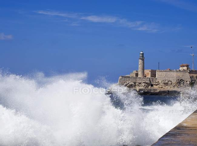 Sea wave breaking at shore with Castillo del Morro, Havana, Cuba — Stock Photo