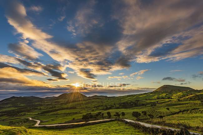 Дорога через зеленой холмистой сельской местности на рассвете с облаками, остров Пико, Азорские острова, Португалия, Европа — стоковое фото
