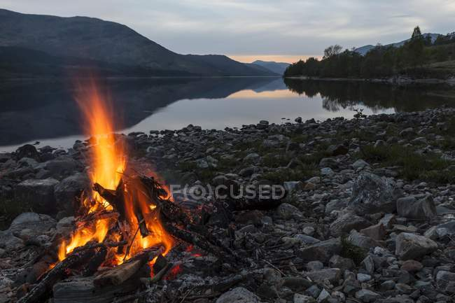 Campfire on shore of lake Loch Arkaig, Fort William, Highlands, Scotland, United Kingdom, Europe — Stock Photo