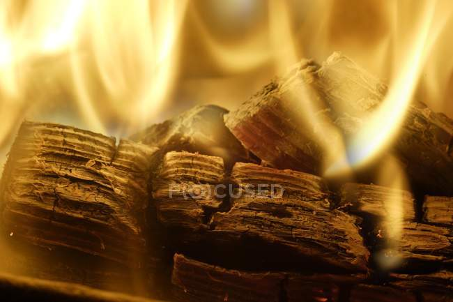 Close-up of burnt logs and fire at fireplace — Stock Photo