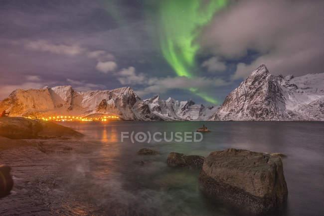 Aurora pequeño con las nubes y las rocas de mar con la ciudad luces y montañas, Isla Hamnoy, Lofoten, Noruega, Europa - foto de stock