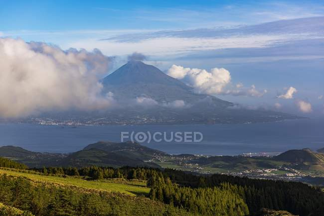 Distant view of volcano Ponta do Pico with clouds, island of Faial, Azores, Portugal, Europe — стоковое фото