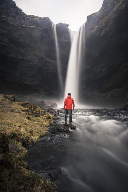 Hombre de chaqueta roja frente a la cascada de Kvernufoss en la garganta en ambiente dramático cerca de Skogafoss, Islandia, Europa - foto de stock