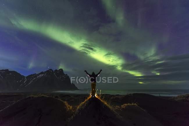 Foto noche de hombre viendo auroras boreales en el macizo de la montaña Klifatindur, Austurland, Islandia - foto de stock