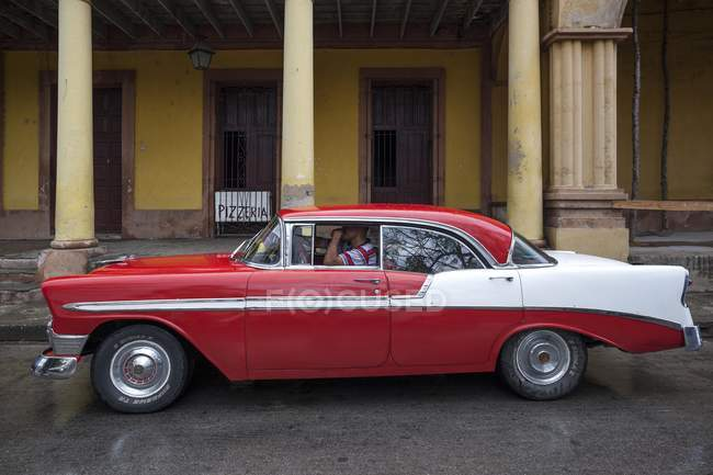 Vintage car in red and white colors on street of Holguin, Holguin Province, Cuba — Stock Photo