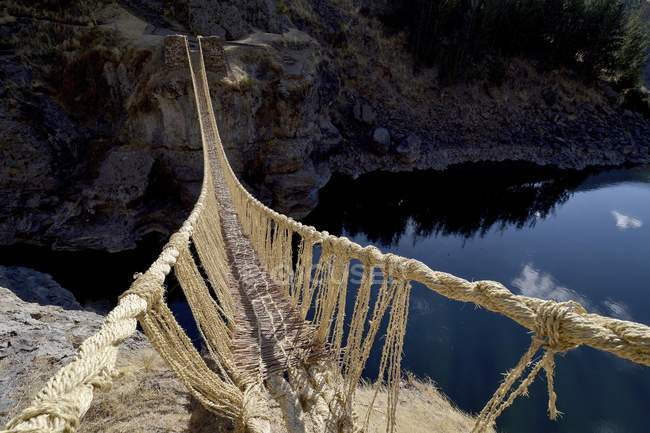 Inca rope bridge made of braided grass across river Apurimac, Peru, South America — стоковое фото