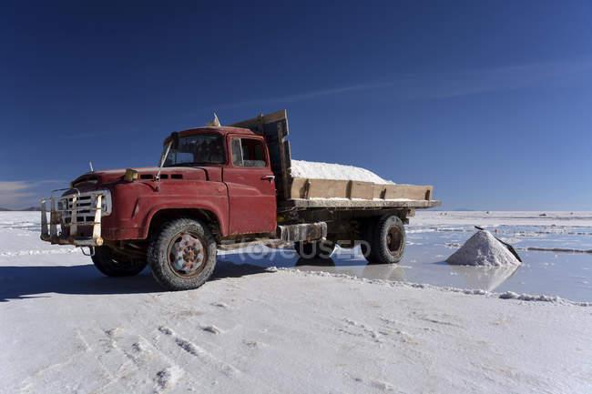 Old truck transporting salt at salt flat of Salar de Uyuni, Altiplano, Bolivia, South America — стоковое фото