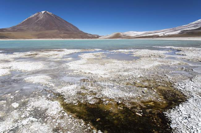 Laguna verde with borax deposits on shore and snow on mountains near Uyuni, Altiplano, border Bolivia and Chile, South America — Stockfoto
